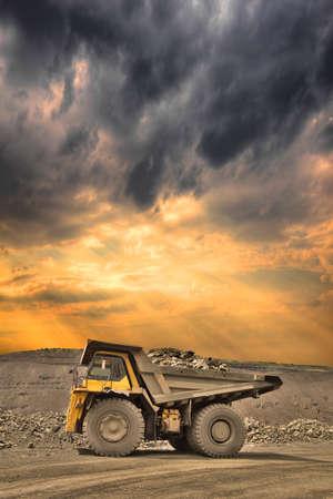 camion minero: Carro de mina pesado cargado con mineral de hierro en la puesta del sol Foto de archivo