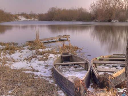 Twee oude vissersboten aan de oever van de rivier op de winter zonsondergang Stockfoto
