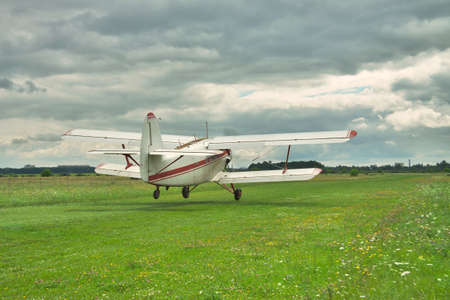 airstrip: Old propeller biplane is taking off grom the grass rough airstrip into the stormy sky