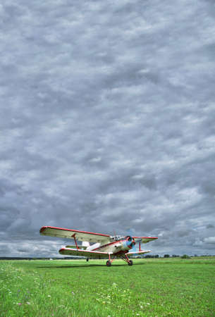 airstrip: Old biplane takeoff from the grass rougn airstrip into the stormy clouds