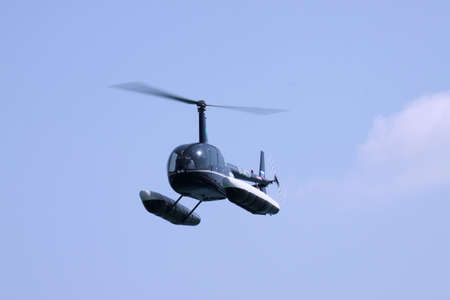floats: Gelendzhik, Russia - September 9, 2010: Robinson R44 helicopter with floats preparing to land on water