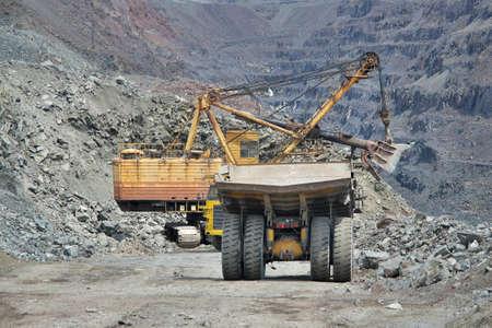 ore: Dump trucks and excavator on the iron ore opencast Stock Photo