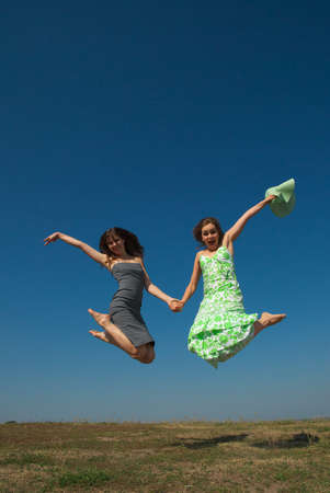 barefooted: Two young happy girls jumping on the hill on a sunny summer day