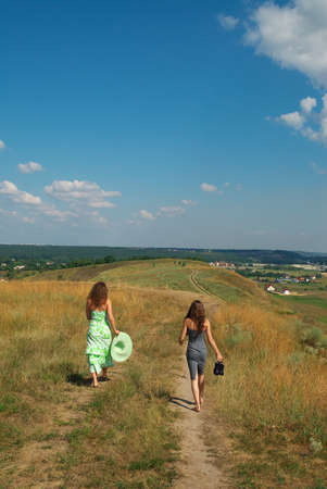 barefooted: Two barefooted girls walking down the hill along the path