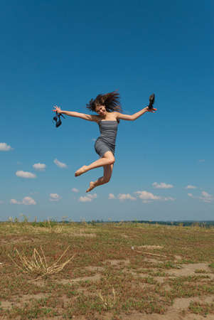 barefooted: A young barefooted girl jumping on top of the hill with the- shoes in her hands Stock Photo