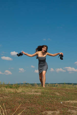 barefooted: Barefooted cheerful girl running on top of the hill with the shoes in her hands Stock Photo