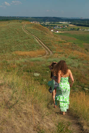 barefooted: Two barefooted girls walking down the hill along the road