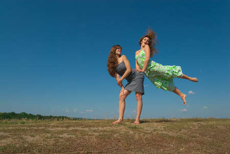 barefooted: Two young happy girls having fun on top of the hill in summer