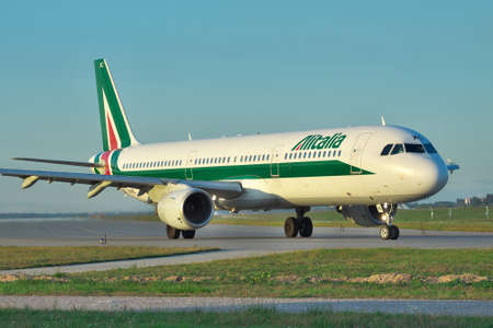 Borispol, Ukraine - Septermber 17, 2011: Alitalia Airbus A321 taxiing to the runway to take off on sunset