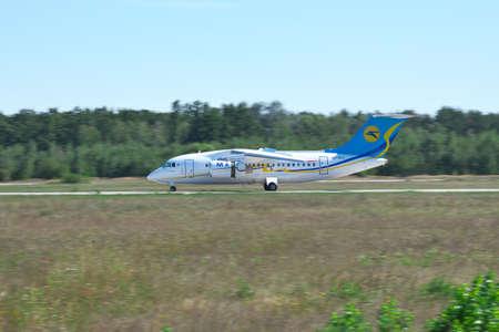 regional: Kiev Region, Ukraine - August 21, 2012: Antonov An-148 regional passenger plane using jet thrust reverser on runway after landing Editorial