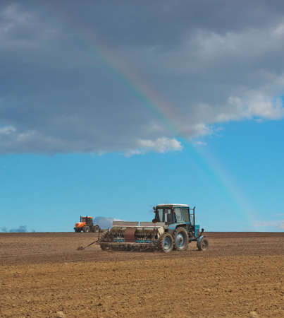sowing: Tractor sowing the field with the seeder and a rainbow in the sky