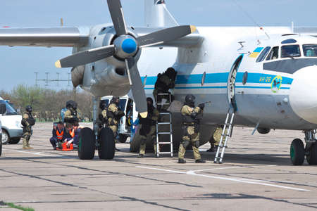 captured: Kiev Region, Ukraine - April 24, 2012: Special operations sercice squad during the counter-terrosist training with a captured aircrafts with medics helipng the victims on the background