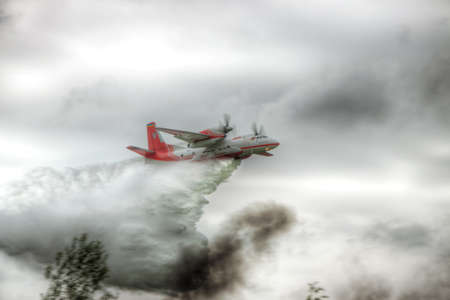 dropping: Nezhin, Ukraine - May 20, 2010: State Emergency Service of Ukraine An-32P firefigher plane is dropping a load of water to the source of forest fires