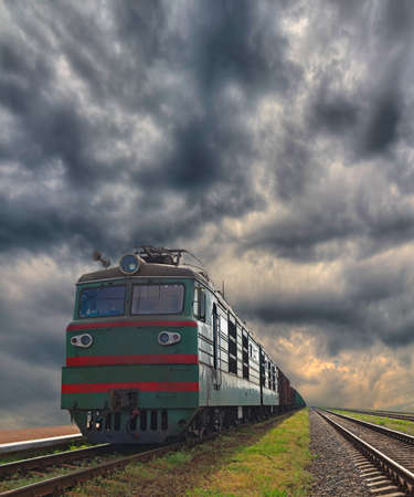 goods train: Cargo train delivering goods with dramatic stormy sky on the background