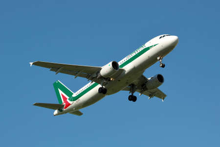 airbus: Borispol, Ukraine - June 9, 2011: Alitalia Airbus A320 is landing against blue sky in summer