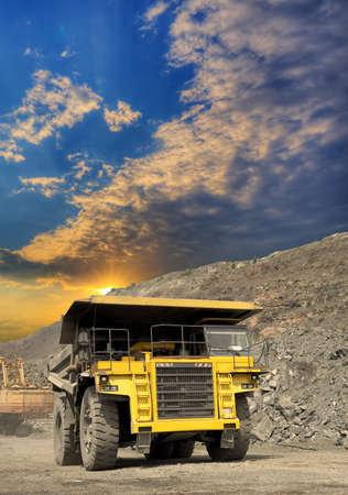 Heavy dump truck transporting iron ore from the opencast on sunset