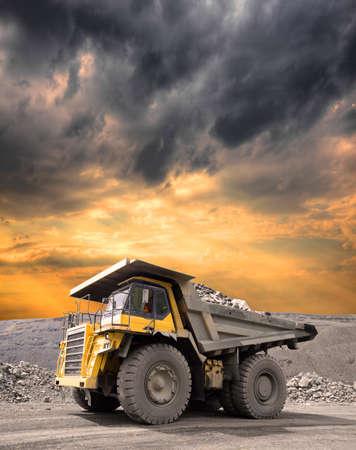 camion minero: De camiones pesados ??de minería a cielo abierto a través de la conducción de mineral de hierro en la puesta del sol tempestuosa Foto de archivo