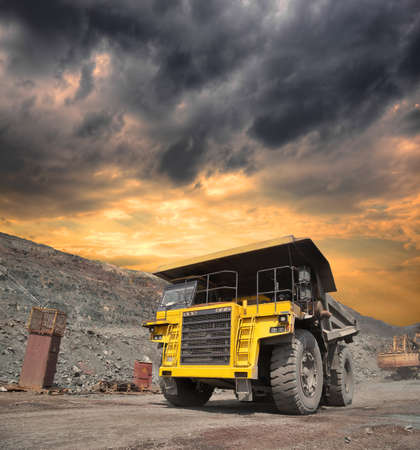 ore: Mining truck loaded withiron ore driving along the opencast on stormy sunset