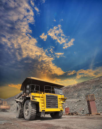 camion minero: Mining truck loaded withiron ore driving along the opencast on sunset