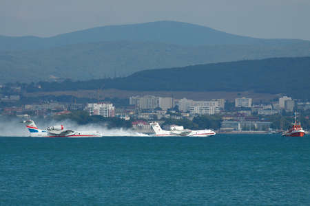 hydroplane: Gelendzhik, Russia - September 8, 2010: A pair of Beriev Be-200 amphibian planes is taking off from water surface of the bay