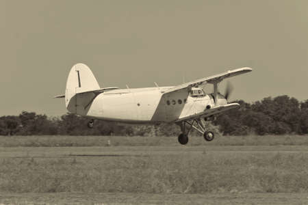 airstrip: Old biplane takeoff from the rough airstrip  black and white image Stock Photo