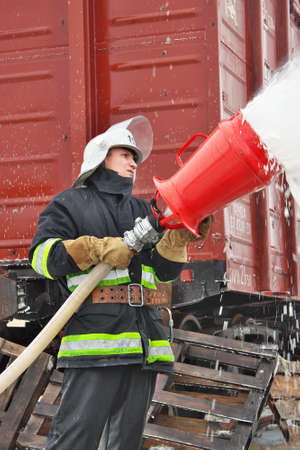 water bus: Chernihiv Region, Ukraine - January 14, 2011: Firefighter is covering the bus with foam after the railway accident training Editorial