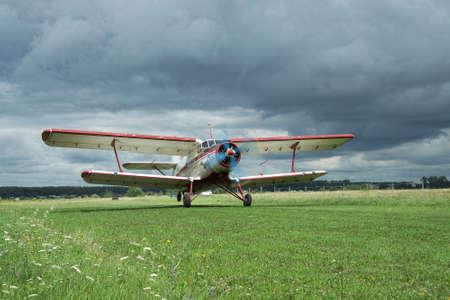 airstrip: Zhitomir, Ukraine - July 31, 2011: Antonov An-2 biplane is taking off from grass airstrip