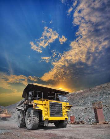 camion minero: Minería camión cargado de mineral withiron conducción a lo largo del cielo abierto en la puesta del sol Foto de archivo