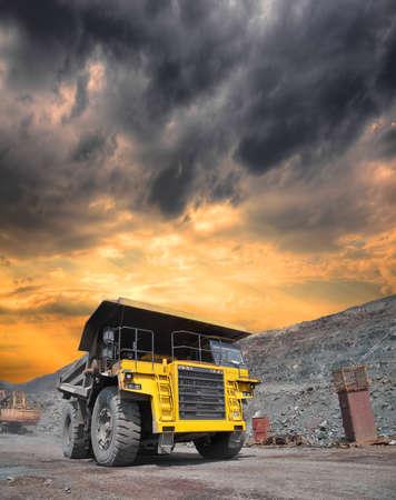 camion minero: Minería camión cargado de mineral withiron conducción a lo largo del cielo abierto en la puesta del sol tempestuosa