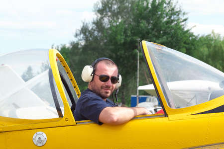 aerobatic: Pilot sitting in the cockpit of a light aerobatic plane with the canopy open