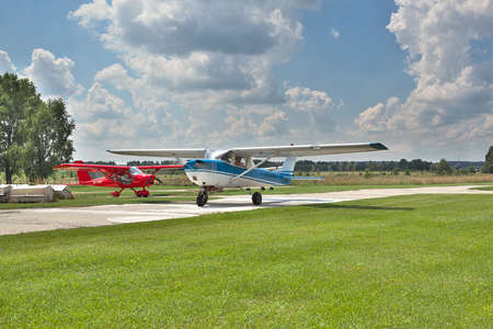 airstrip: Kiev Region, Ukraine - July 20, 2014: Light private planes on the airfield on a sunny day performing leisure flights. Cessna 150 two-seat general aviation plane on the front