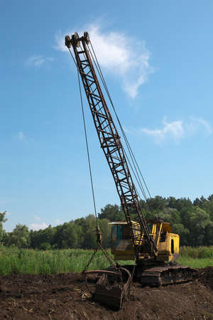 Excavator developing the peat on the swamp