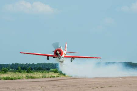 Zhitomir, Ukraine - June 17, 2011: Yakovlev Yak-52 aerobatic plane passing low over the runway