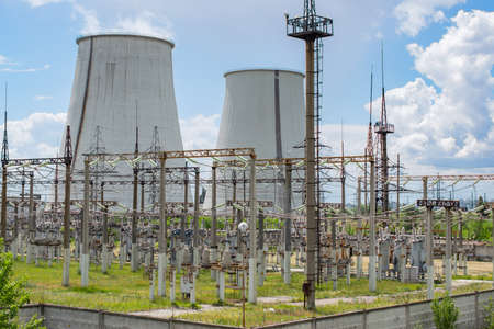 transformator: Power plant transformator station with cooling towers on the background