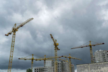 Construction cranes developing residential buildings under the stormy sky Imagens