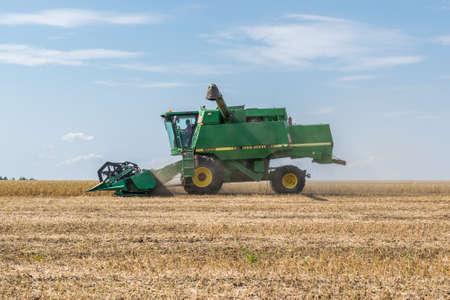 Kiev Region, Ukraine - September 10, 2017: John Deere 9500 Harvester is harvesting the soybean field on a summer autumn day