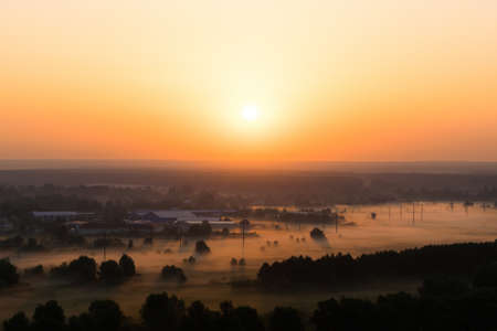 Sunset over the village in summer with fog in the valley