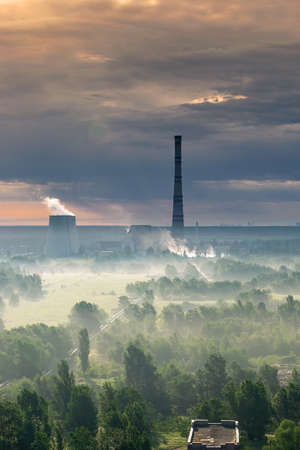 Power plant on sunrise in the valley covered with fog and stormy clouds on the background