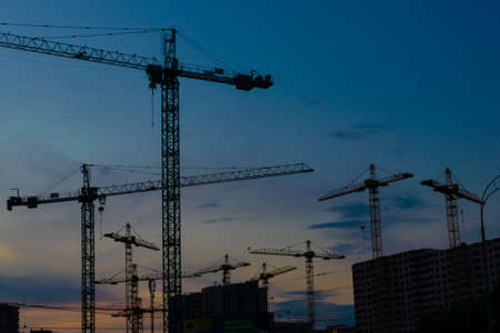 Group of construction cranes developing the buildings with sunset sky on the background Imagens