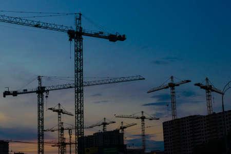 Gruppe von Baukränen, die die Gebäude mit Sonnenuntergangshimmel im Hintergrund entwickeln Standard-Bild