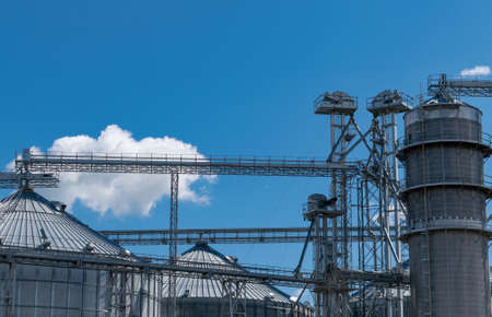 Grain elevator silos closeup with blue sky on the background