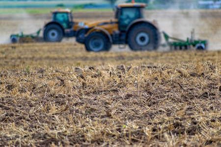 Fresh tillage on the field and two defocufed tractors with cultivator on the background Stok Fotoğraf