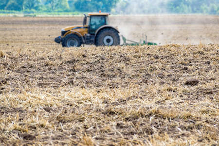 Fresh tillage on the field and a defocufed yellow tractor on the background