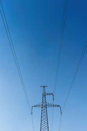 Power line mast against deep blue sky background