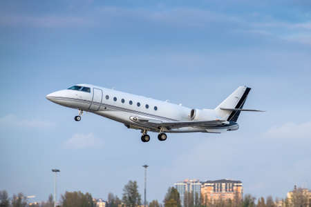 Business jet is taking off at dusk with cityscape on the background