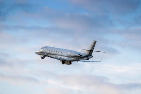 Business jet is taking off on sunset with clouds