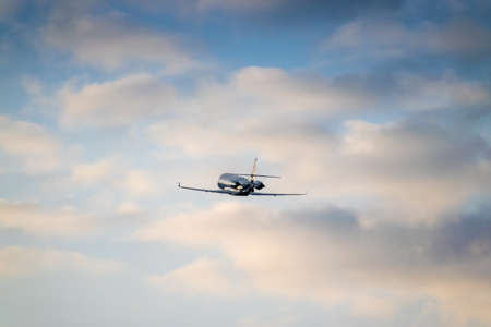 Business jet is taking off on sunset with rising clouds