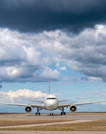 Passenger jet plane on the runway in the airport with rising storm on the background Stock Photo