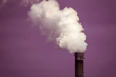 Air pollution with heavy smoke or vapor from the chimney with purple sky background Stock Photo
