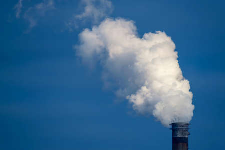 Air pollution with heavy smoke or vapor from the chimney with blue sky background Zdjęcie Seryjne